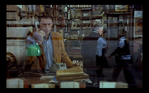 As we can see from the reflection on the window, the image dissolves into another filmed outside the bookshop so we can't hear the phone conversation and so that the outside world is reflected as happening outside the emotional turmoil happening inside