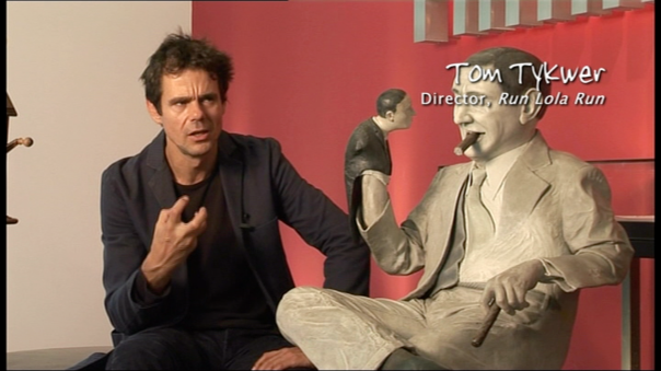 Tom Tykwer next to a statue of Lubitsch