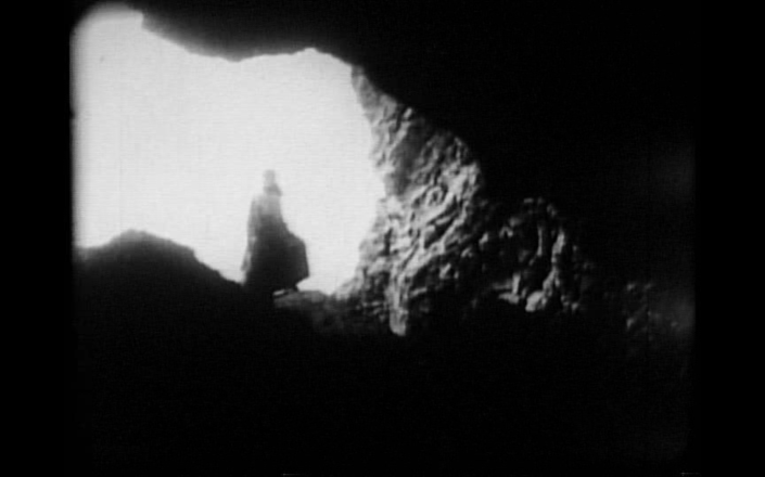 Pola approaching, as seen from inside the cave in a striking composition,